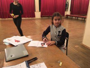 Ученица I курса школы «Плащ и шпага» София подписывает свою зачетную книжку